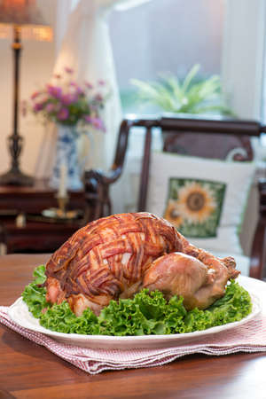 antique vase: Thanksgiving Turkey Dinner. Roast turkey covered with bacon bacon. Retro  antique setup. Antique furniture, pink daisy flowers in  antique blue and white china vase.