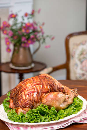 antique: Thanksgiving Turkey Dinner. Roast turkey covered with bacon bacon. Retro  antique setup. Antique furniture, pink daisy flowers in  antique blue and white china vase.