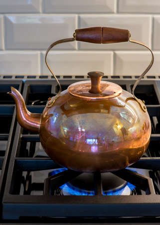 gas stove: Antique copper kettle on gas stove burner. Shinny surface, wood knob and handle. Afternoon tea time.
