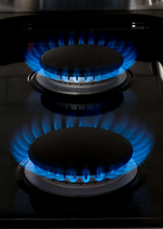 oven range: New gas stove burners. Pure blue flames burning in dark background. Stock Photo