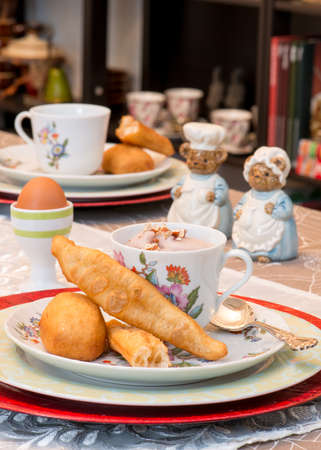 antique asian: Asian  Chinese breakfast table background. Fried dough stick and mashed eddo sprinkled with pecan crumbs.  Antique pepper and salt shakers. Vintage  Antique teacups and pot.