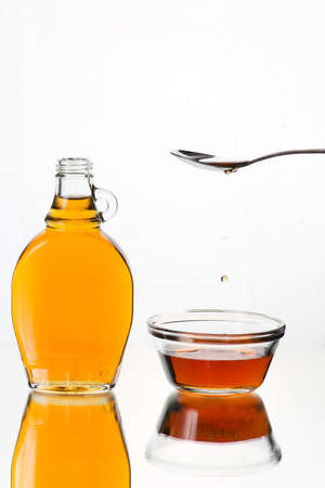 grades: Maple Syrup dripping from a spoon, isolated in white background. Canada Category No. 1 light and medium grades.  High speed flash photography. Stock Photo