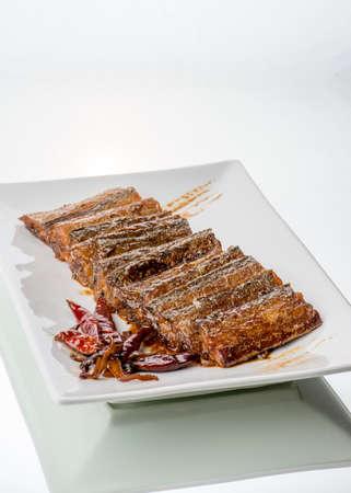 scheide: Scabbard Fisch in pikanter Soße dunkel, auf Glastisch gekocht. Weißer Hintergrund. Lizenzfreie Bilder