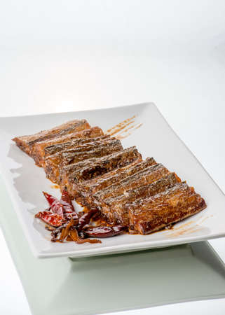 chinese meal: Scabbard fish cooked in spicy dark sauce, on glass table. White background.
