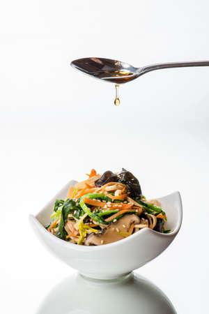 chinesisch essen: Sesam�l auf asiatischen sauted Gem�sesalat betr�ufelt. �ltr�pfchen in der Luft gefroren.