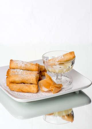 gourmet food: rollitos de primavera con relleno dulce, salsa de leche condensada, en la mesa de cristal. Fondo blanco. Foto de archivo