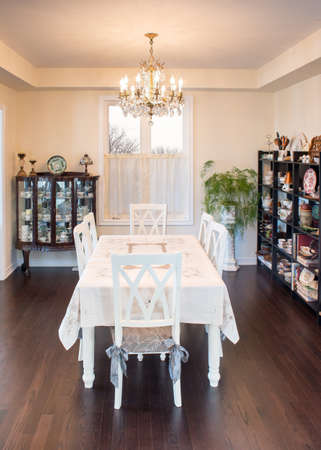 curio: Retro style dining room in warm light. Curio and shelves full of collectibles; Antique brass chandelier; Chalk paint table and chairs; Lace fabric table cloth. interior design. Stock Photo