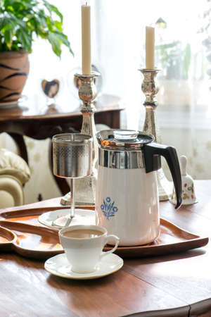 tarde de cafe: Brewing coffee with vintage stove top percolator. Antique walnut tea table, vintage white bone china teacups, mahogany leaf tray from Haiti. Antique silver candle sticks. Warm afternoon sun light.