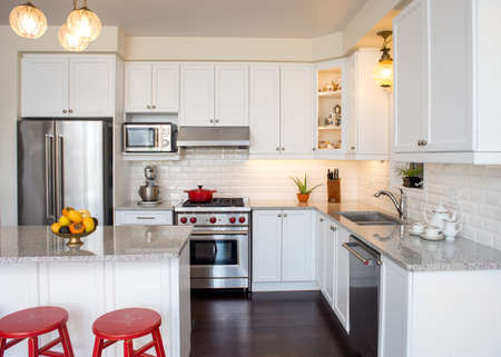 professionally: Professionally designed new kitchen with touch of retro. Professional gas range and hood, white cabinet,  antique ceiling lamp, fine bone china teacups in cabinets. Chalk paint. Interior design ideas.