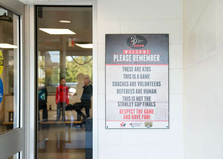 plea: Ennismore Canada - October 15, 2016:A framed sign, as a plea to hockey parents for fair play codes, hangs on the wall outside the door of the community center arena during a minor hock game.