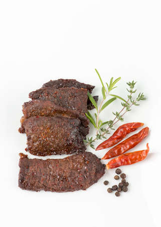 caribbeans: Beef jerky on white background. Rosemary, thyme , black pepper corns and red hot chill peppers on the side.