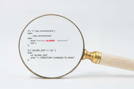 debugging: Antique brass magnifier with bone  ivory handle magnifies short unix scripts. Text in focused  shows the word Alert. Audit, compliance, regulation, data reconciliation, software debugging concept. Stock Photo