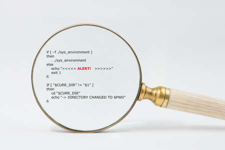 debugging: Antique brass magnifier with bone  ivory handle magnifies short unix scripts. Text in focused  shows the word Alarm. Audit, compliance, regulation, data reconciliation, software debugging concept. Stock Photo