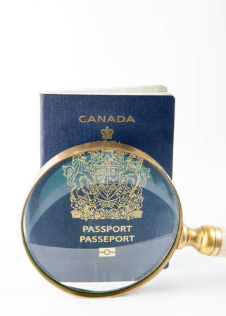 forgery: Canadian passport under magnifying glass scrutiny. Security awareness.