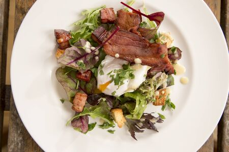 softly: Salad Lyonnaise with pancetta, crisp leaves, softly poached egg, croutons & creamy dressing Stock Photo