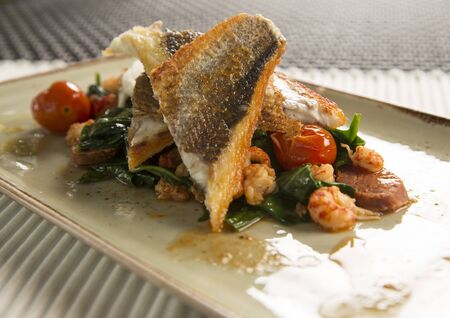 baby spinach: Pan fried sea bass with crayfish, chorizo, baby spinach & cherry tomatoes Stock Photo