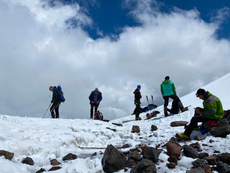 ELBRUS DISTRICT, RUSSIA - JULY 7, 2020: A group of climbers with backpacks and trekking poles stands and rests on a snowy trail. Snowy slopes of the northern Elbrus region. Mountain winter landscape.