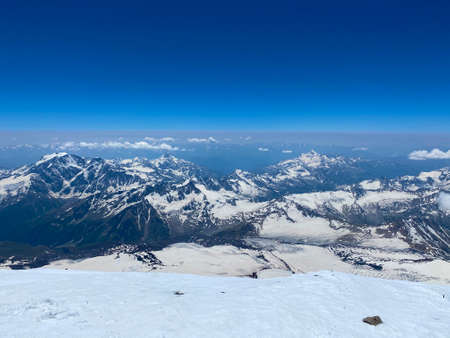 A breathtaking view from the top of Elbrus. Beautiful winter mountain landscape. Snowy rocky slopes of the northern Elbrus region. Blue sky Imagens