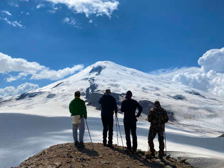 Four climbers stand on a hill and look at Mount Elbrus. Aerial view of a beautiful mountain winter landscape. Snowy rocky slopes of the northern Elbrus region.