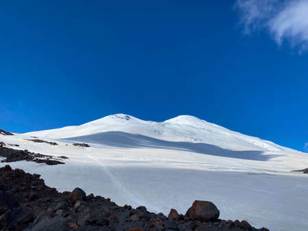 Mount Elbrus. Aerial view of a beautiful winter mountain landscape. Snowy rocky slopes of the northern Elbrus region. Blue sky with white clouds. Imagens