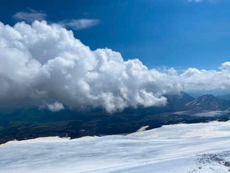 Aerial view of a beautiful winter mountain landscape. Snowy rocky slopes of the northern Elbrus region. Blue sky with white clouds.