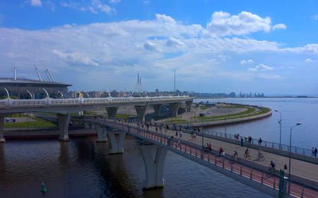 ST. PETERSBURG, RUSSIA - JUNE 7, 2020: Aerial view of the longest pedestrian bridge in St. Petersburg. People on the bridge. Drone flight over the city and the Gulf of Finland.