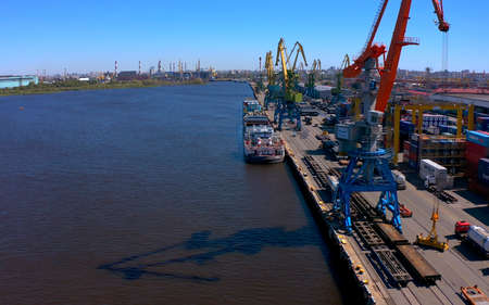 SAINT PETERSBURG, RUSSIA - JULY 17, 2020: Aerial view of a row of construction or cargo cranes on the river bank with a boat sailing nearby. Ship docks off Kanonersky Island. Industrial port with water barges and transport tugs.