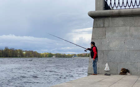 ST. PETERSBURG, RUSSIA - MAY 13, 2020: A man catches fish on the embankment near the Black River on a cloudy day in the city. Editorial