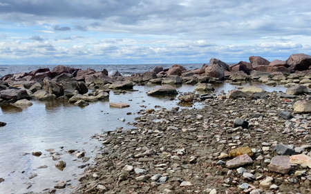 Rocky seashore. Beautiful sea with small waves. The waves beat against the stones. Imagens