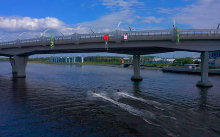 ST. PETERSBURG, RUSSIA - JUNE 7, 2020: Guys ride jet skis under the bridge. Drone flight over the beautiful ocean. Boat trip on a summer day.