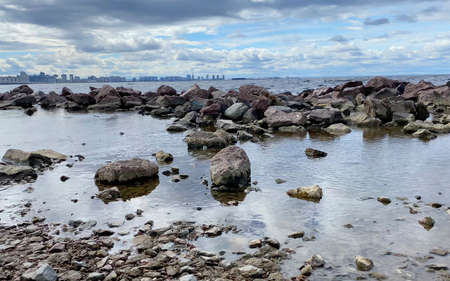 Rocky seashore with a city in the distance. Beautiful sea with small waves. The waves beat against the stones. Imagens