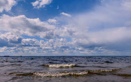 Beautiful blue sea with small waves and a blue sky with white clouds. Nature summer ocean background. Imagens