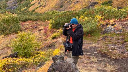 A traveler photographer takes a photo of the amazing nature of Kamchatka. Trekking in the Klyuchevskoy volcano park. Travel to the Kamchatka Peninsula. 写真素材