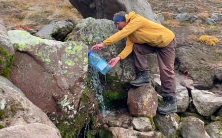 The traveler collects mountain water in a large plastic bottle. Mountain climbing. Trekking in the Klyuchevskoy volcano park. Travel to the Kamchatka Peninsula.
