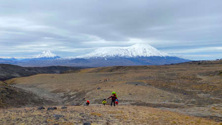 Several travelers with large backpacks are walking along the endless fields of the tundra. Trekking in the Klyuchevskoy volcano park. Travel to the Kamchatka Peninsula. 写真素材