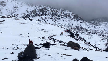 Group of climbers descends from a snowy mountain. Trekking in the Klyuchevskoy volcano park. Travel to the Kamchatka Peninsula. 写真素材