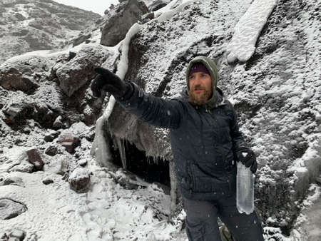 A traveler with a beard and a bottle of water points to something. Trekking in the Klyuchevskoy volcano park. Travel to the Kamchatka Peninsula.