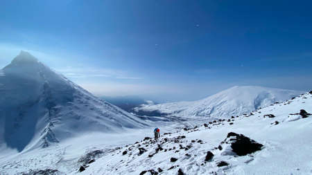 A tourist climbs the Klyuchevskaya Sopka volcano along a snow-covered path past stones. Trekking in the Klyuchevskoy volcano park. Travel to the Kamchatka Peninsula. 写真素材