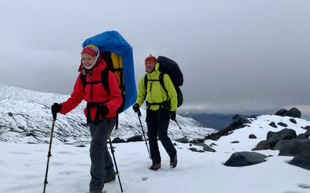 Two climbers with large backpacks and trekking poles are walking along the snowy trail. Mountain climbing. Trekking in the Klyuchevskoy volcano park. Travel to the Kamchatka Peninsula.
