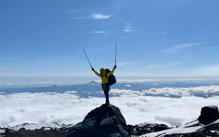 A climber with trekking poles is standing on the top of a volcano. Mountain climbing. Trekking in the Klyuchevskoy volcano park. Travel to the Kamchatka Peninsula.