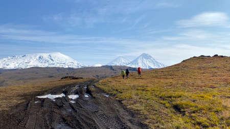 Three tourists with big backpacks and trekking poles go to the volcanoes of Kamchatka. Trekking in the Klyuchevskoy volcano park. Travel to the Kamchatka Peninsula. 写真素材