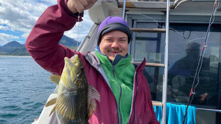 Fisherman caught a perch with a fishing rod. Boat trip on a boat along the Avacha Bay. Fishing in the Pacific Ocean off the Kamchatka Peninsula.
