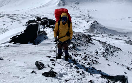 Climber in a yellow jacket with an ice ax goes to the top of the volcano along a snow-covered trail. Mountain climbing. Trekking in the Klyuchevskoy volcano park. Travel to the Kamchatka Peninsula. 写真素材