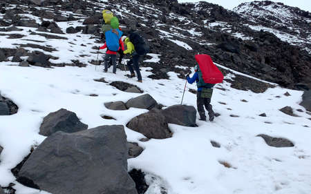 Several climbers with large backpacks and trekking poles go to the top of the volcano. Mountain climbing. Trekking in the Klyuchevskoy volcano park. Travel to the Kamchatka Peninsula.