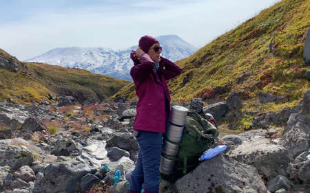 Woman tourist with a large backpack at a halt. Mountain climbing. Trekking in the Klyuchevskoy volcano park. Travel to the Kamchatka Peninsula. 写真素材