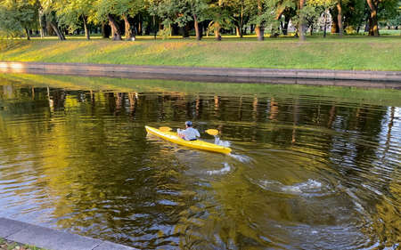 A young man with a paddle floats on a yellow kayak. Morning boat trip in the historical center of St. Petersburg by kayak.