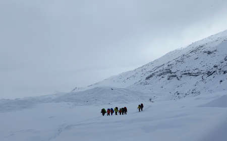 Tourist climbers with large backpacks and trekking poles are walking along the snow-capped mountains. Mountain climbing. Trekking in the Klyuchevskoy volcano park. Travel to the Kamchatka Peninsula.