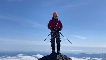 A climber with trekking poles stands on the top of the mountain. Trekking in the Klyuchevskoy volcano park. Travel to the Kamchatka Peninsula.