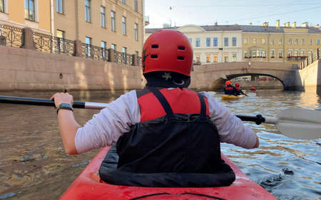 SAINT PETERSBURG, RUSSIA - AUGUST 17, 2020: A girl with an oar floats on a red kayak, view from the back. Morning boat trip in the historical center of St. Petersburg by kayak.