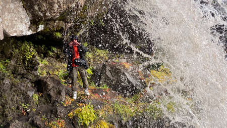 A photographer stands under a beautiful waterfall and takes pictures. Stunning autumn landscape. Beautiful place. Travel to the Kamchatka Peninsula.